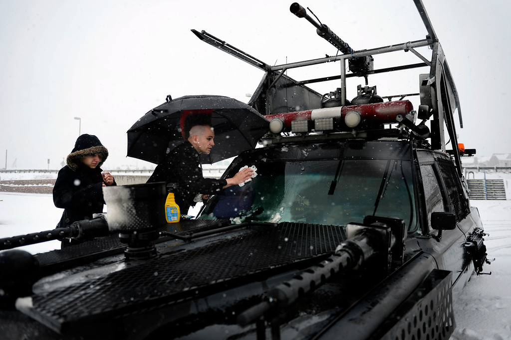 . ARVADA, CO. - MARCH 09: Zach Helm and Sara Heisley clean off the windshield of Alexi at the park and ride on 88th and Wadsworth Ave in Arvada as the snow continues to fall on their way to the Frozen Dead Guy Days in Nederland, Colorado March 09, 2013. Arvada, Colorado. (Photo By Joe Amon/The Denver Post)