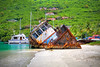 Old sunk tug boat on the shoreline of a beautiful tropical beach.