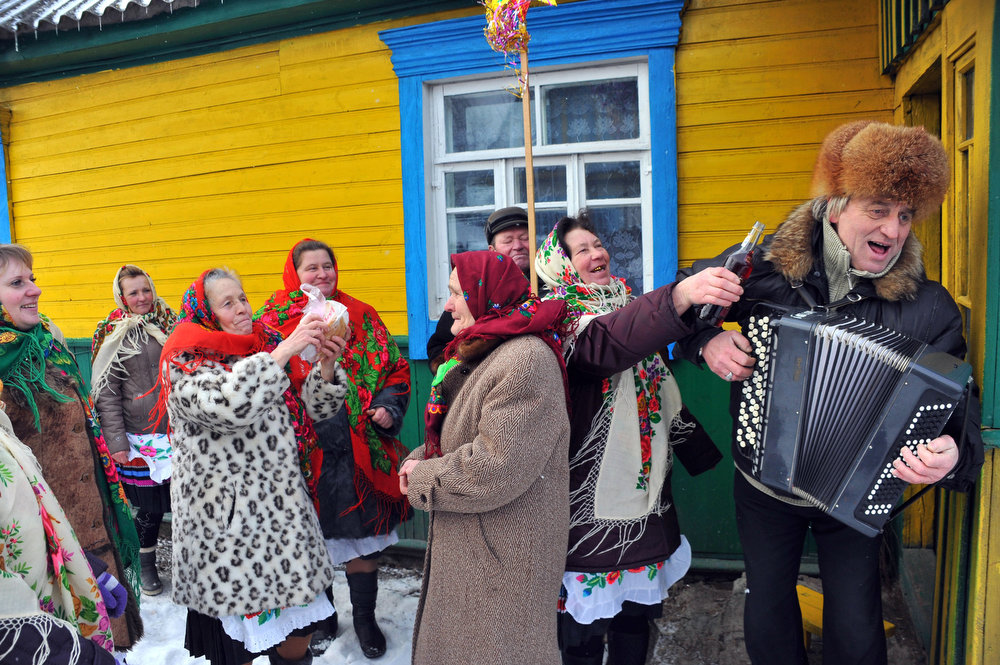 . A man plays the accordion as people gathered during Christmas celebration in the town of Richev, some 290 km south from Minsk. on January 7, 2013. Orthodox Christians celebrate Christmas on January 7 in the Middle East, Russia and other Orthodox churches that use the old Julian calendar instead of the 17th-century Gregorian calendar adopted by Catholics, Protestants, Greek Orthodox and commonly used  attendsin secular life around the world.   AFP PHOTO / VIKTOR  DRACHEV/AFP/Getty Images