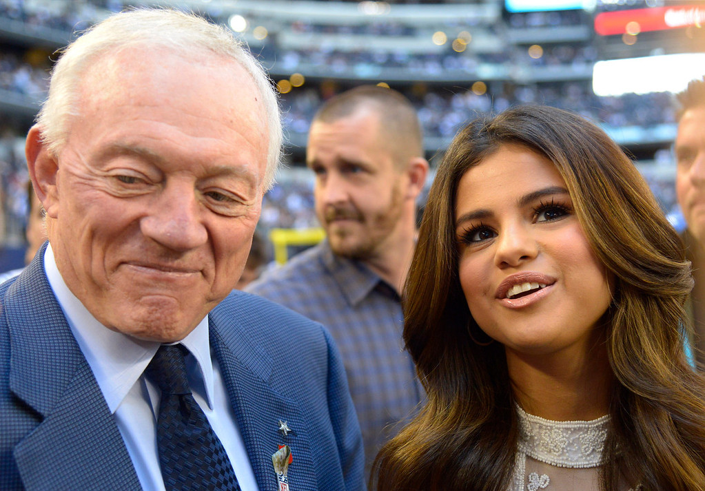 . Dallas Cowboys team owner Jerry Jones gives a television interview with entertainer Selena Gomez, right, on the field before an NFL football game against the Minnesota Vikings, Sunday, Nov. 3, 2013, in Arlington, Texas. Gomez will be the half time entertainment on Thanksgiving Day when the Cowboys take on the Oakland Raiders. (AP Photo/Tim Sharp)