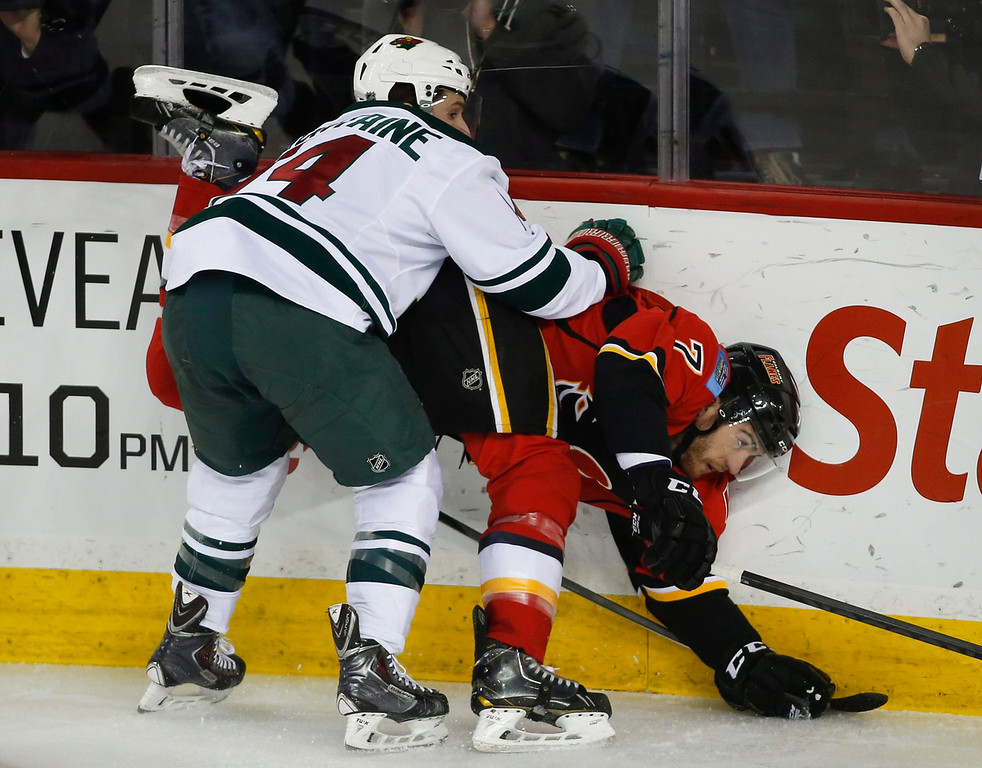 . Minnesota Wild Justin Fontaine, left, dumps Calgary Flames\' TJ Brodie during second period of an NHL hockey game in Calgary, Alberta, Saturday, Feb. 1, 2014. (AP Photo/The Canadian Press, Jeff McIntosh)