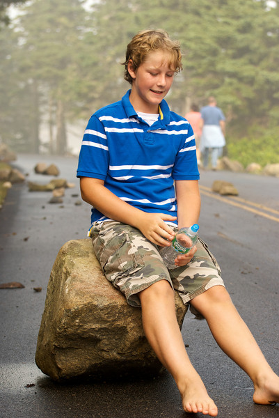 Ten year-old sitting on a rock tossed by the waves.