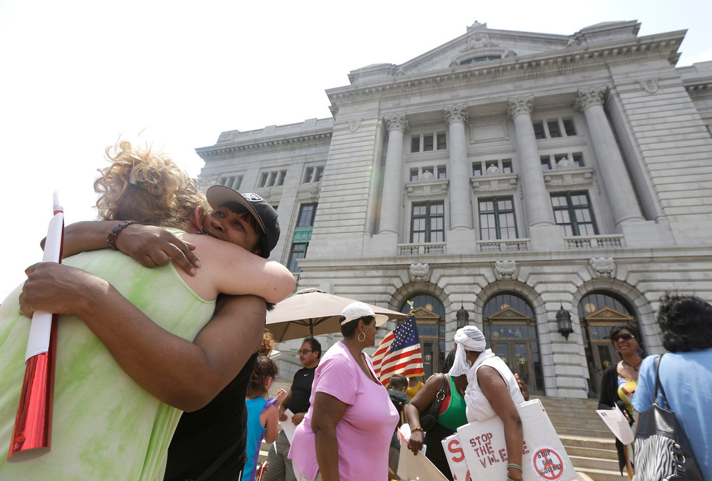 """. Ada Wideman and Elaine Maldonado embrace during a rally outside of William T. Brennan Courthouse, Saturday, July 20, 2013, in Jersey City, N.J. Maldonado, who met Wideman at the rally, gave her a peace bracelet she was wearing to Wideman as gift. The Rev. Al Sharpton\'s National Action Network organized \""""Justice for Trayvon\"""" rallies nationwide to press for federal civil rights charges against George Zimmerman, who was found not guilty in the shooting death of unarmed teenager Trayvon Martin. (AP Photo/Julio Cortez)"""