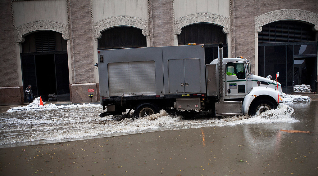 . A truck drives through a flooded street, caused by Hurricane Sandy, near the north side of Ground Zero on October 30, 2012 in the Financial District of New York, United States. The storm has claimed at least 33 lives in the United States, and has caused massive flooding across much of the Atlantic seaboard. US President Barack Obama has declared the situation a \'major disaster\' for large areas of the US East Coast including New York City. (Photo by Andrew Burton/Getty Images)