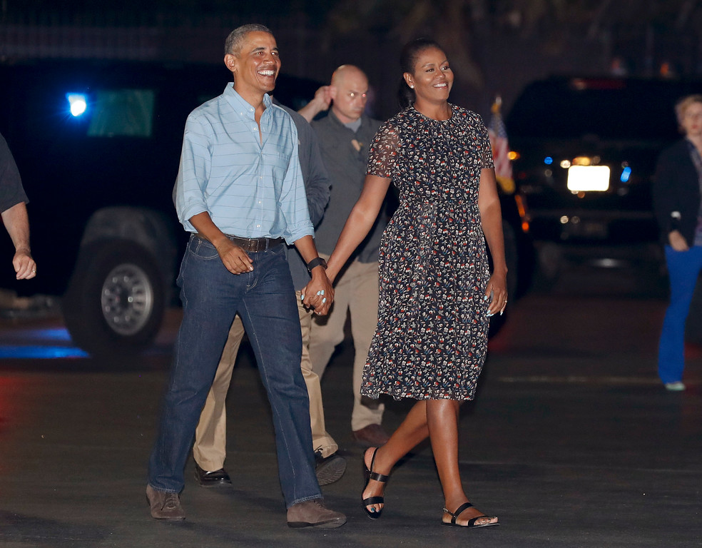 . U.S. President Barack Obama and first lady Michelle Obama walk to board Air Force One, Sunday, Jan. 1, 2017, at Joint Base Pearl Harbor-Hickam, adjacent to Honolulu, Hawaii, en route to Washington after their annual family vacation on the island of Oahu. (AP Photo/Carolyn Kaster)
