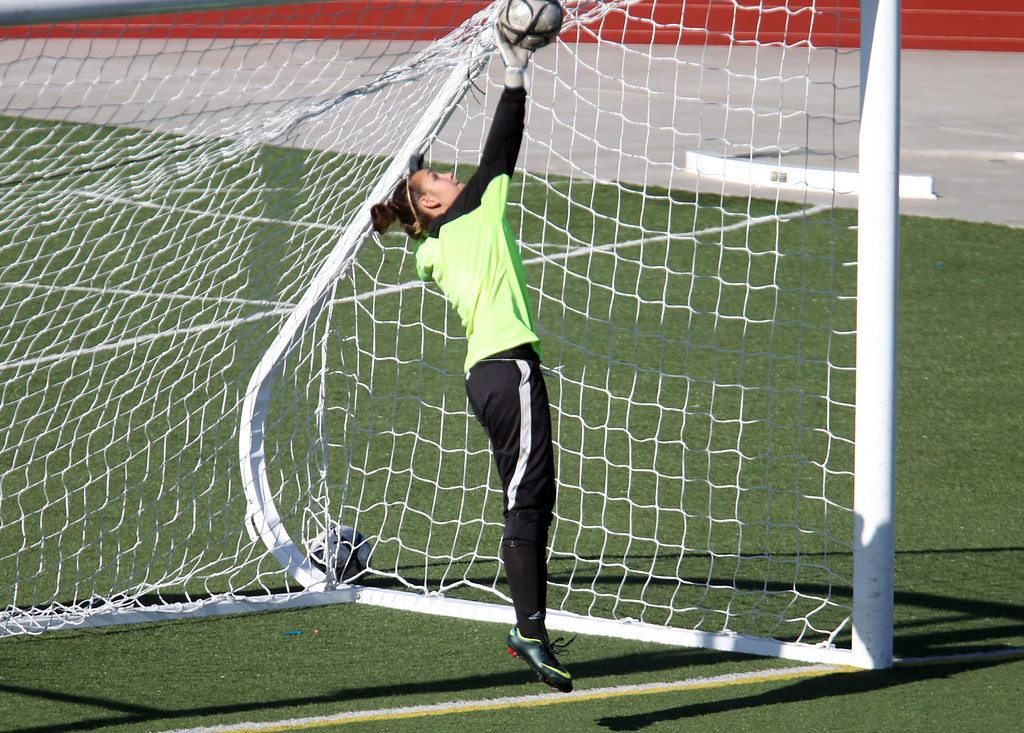 . Piedmont goalie Kesy Platt makes a save on a header by Bishop O\'Dowd\'s Ryan Walker-Hartshorn (7) in the second half of overtime of their North Coast Section Division II Girls Soccer Championship at Dublin High School soccer field in Dublin, Calif., on Saturday, Feb. 23, 2013. Bishop O\'Dowd won 3-2 in a series of penalty kicks. (Ray Chavez/Staff)