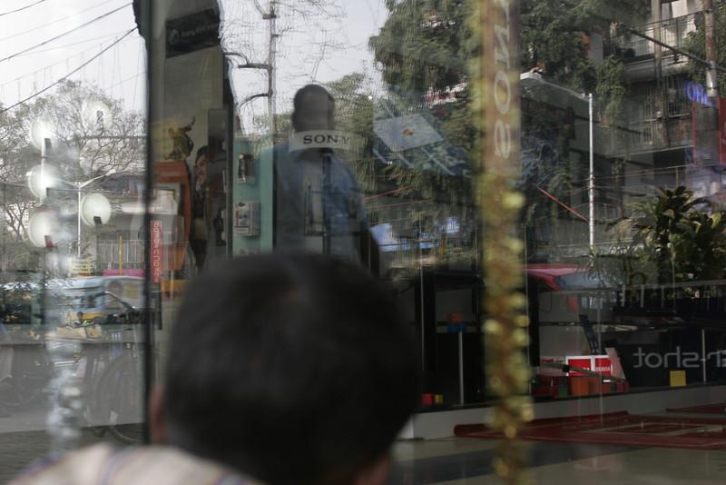 Kid watching tv through the window shop, Calcutta, Kolkata