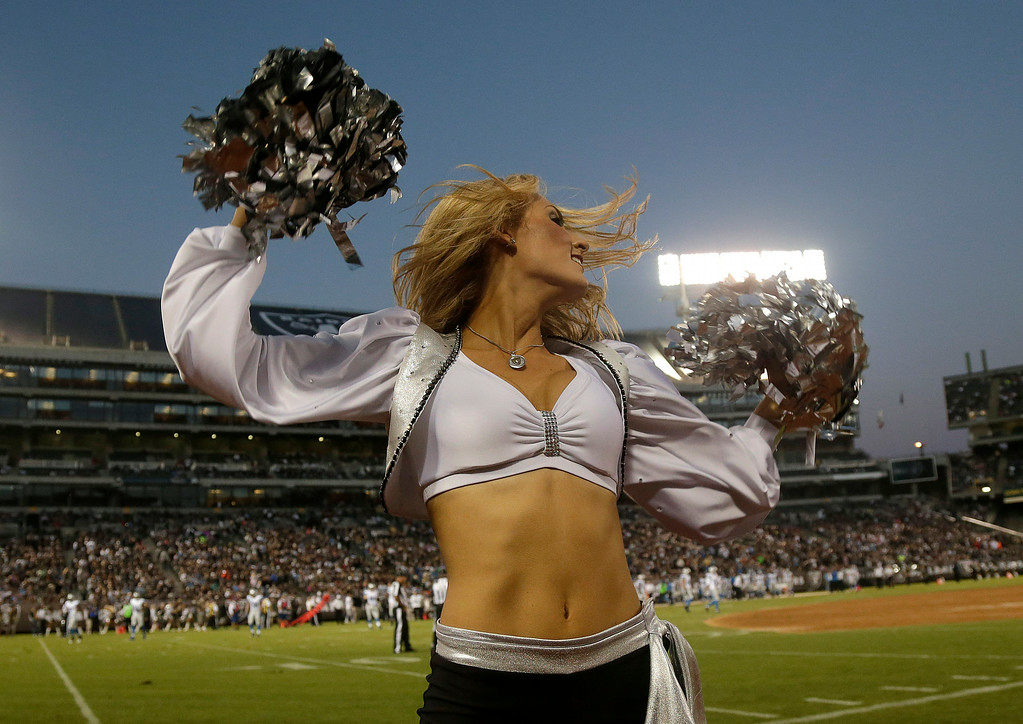 . An Oakland Raiders cheerleader performs during an NFL preseason football game against the Detroit Lions in Oakland, Calif., Friday, Aug. 15, 2014. (AP Photo/Marcio Jose Sanchez)