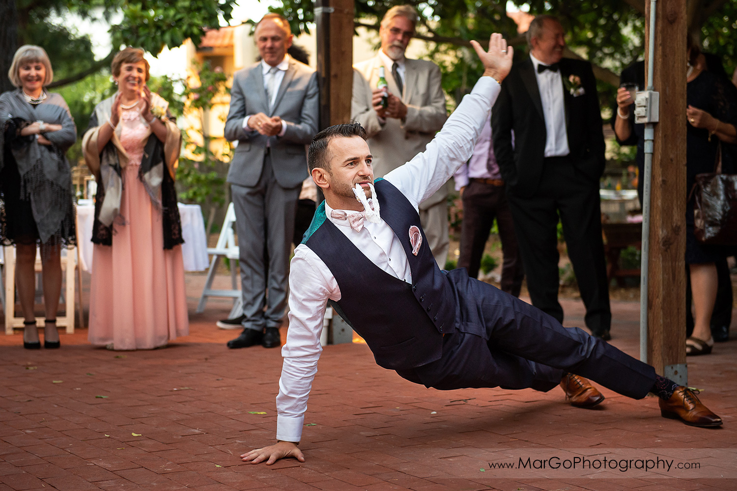 groom with white garter in mouth during wedding reception at San Pablo Rockefeller Lodge