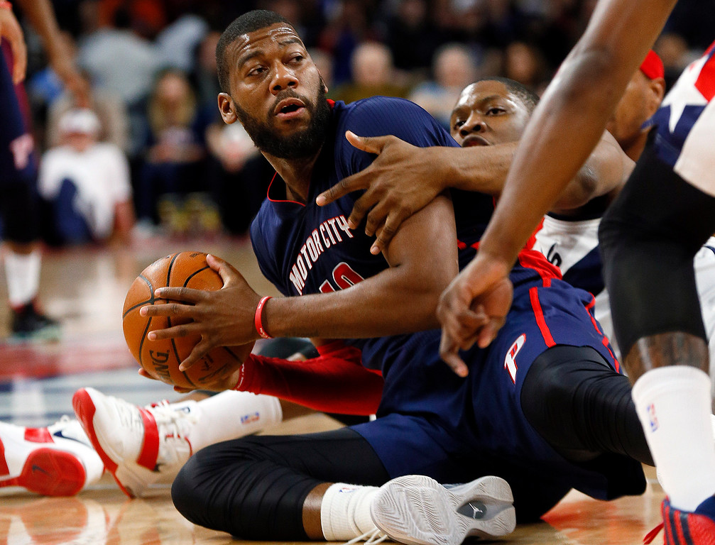 . Detroit Pistons forward Greg Monroe (10) looks to pass from the floor as Washington Wizards center Kevin Seraphin (13) defends in the first half of an NBA basketball game in Auburn Hills, Mich., Sunday, Feb. 22, 2015. (AP Photo/Paul Sancya)