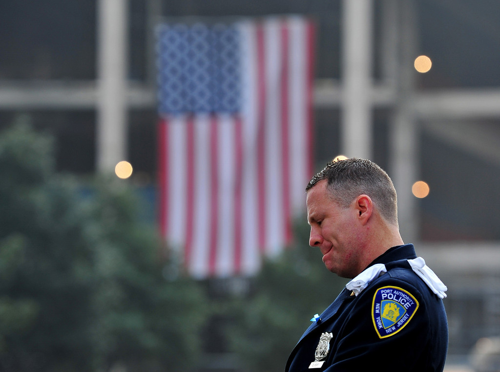 . Daniel Henry, a Port Authority of New York/New Jersey police officer, pauses during a moment of silence at 9:01 am EDT, at the South reflecting pool of the 9/11 Memorial during ceremonies for the twelfth anniversary of the terrorist attacks on lower Manhattan at the World Trade Center site on September 11, 2013 in New York City.  (Photo by Stan Honda-Pool/Getty Images)