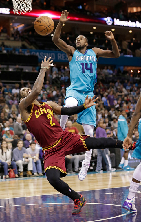 . Cleveland Cavaliers\' Kyrie Irving (2) shoots after being fouled as he drives past Charlotte Hornets\' Michael Kidd-Gilchrist (14) during the second half of an NBA basketball game in Charlotte, N.C., Friday, Jan. 2, 2015. The Cavaliers won 91-87. (AP Photo/Chuck Burton)