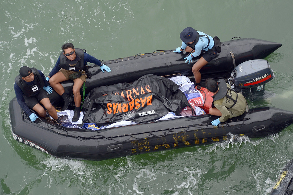 . Indonesian Navy personnel carry a plastic bag containing the dead body of a passenger of AirAsia Flight 8501 at sea off the coast of Pangkalan Bun, Indonesia, Saturday, Jan. 3, 2015. Indonesian officials were hopeful Saturday they were honing in on the wreckage of the flight after sonar equipment detected two large objects on the ocean floor, a full week after the plane went down in stormy weather. (AP Photo/Adek Berry, Pool)