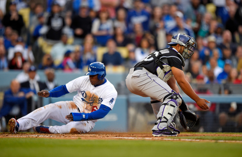 . Los Angeles Dodgers\' Yasiel Puig scores on a sacrifice fly by Adrian Gonzalez as Colorado Rockies catcher Wilin Rosario takes a late throw during the third inning of a baseball game, Saturday, April 26, 2014, in Los Angeles. (AP Photo/Mark J. Terrill)