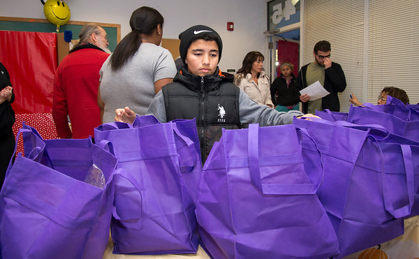 11/25/19 Wesley Bunnell | StaffrrThanksgiving meals were handed out by HRA Bristol on Monday evening by workers and volunteers. Volunteer Juan Martinez helps pass out bags filled with meal ingredients.
