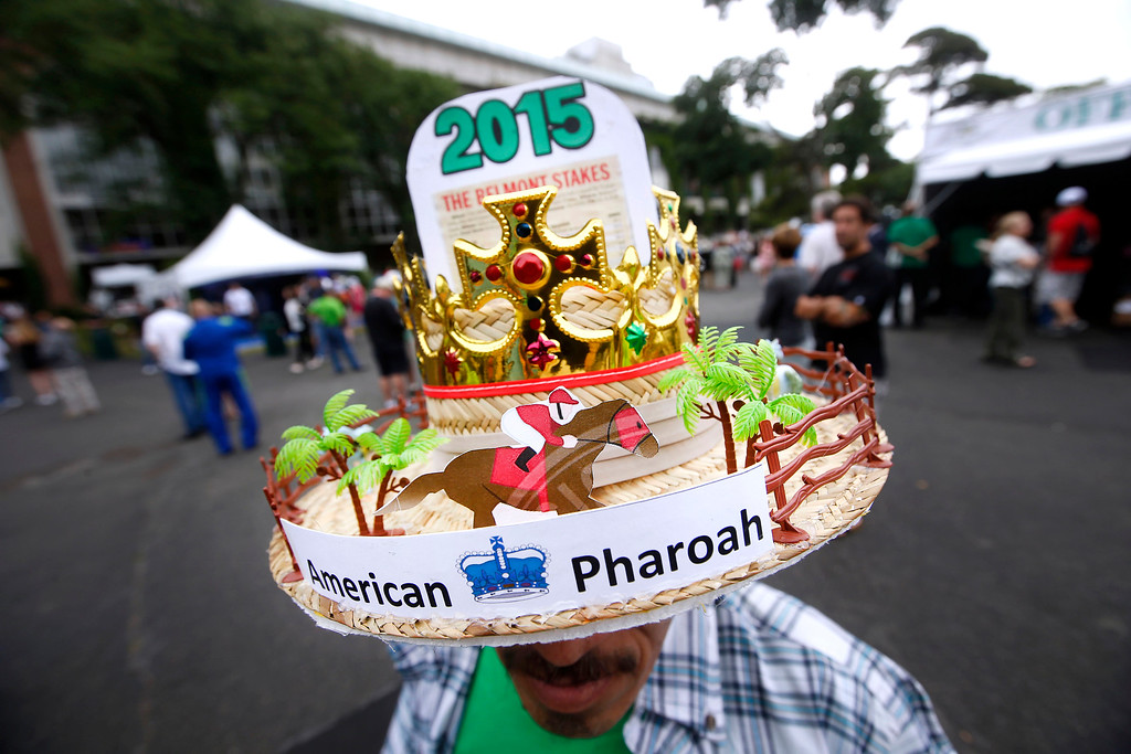 . Edwin Collazo, of the Brooklyn borough of New York, wears an American Pharoah hat before the 147th running of the Belmont Stakes horse race at Belmont Park, Saturday, June 6, 2015, in Elmont, N.Y.  American Pharoah will try for a Triple Crown when he runs in Saturday\'s race. (AP Photo/Jason DeCrow)