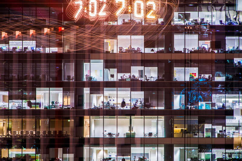 This is what happens when you accidentally kick the tripod during a long exposure.    I was photographing the bright clean modern office atmosphere when the tripod moved the camera to focus on the clock on top of the buildign next door.