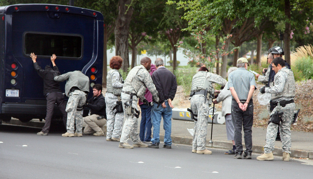 . Demonstrators are searched and processed after being arrested in Livermore, Calif. on Tuesday, Aug. 6, 2013, by an officers from Lawrence Livermore Laboratory\'s protective forces at a protest of nuclear weapons at the lab on the 68th anniversary of the atomic bombings of Hiroshima and Nagasaki during WWII.  (Jim Stevens/Bay Area News Group)