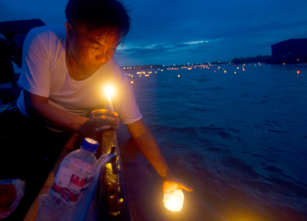. A man releases paper lantern with tiny candle to float at Shwe Kyin creek during light festival on Friday, Oct. 6, 2017, in Bago, about 183 km from Yangon, Myanmar. Myanmar Buddhists lighted up the sky with fireworks and released paper lanterns down the creek in a ritual believed to bring good fortune during annual light festival celebrating at the end of Buddhist Lent. (AP Photo/Thein Zaw)
