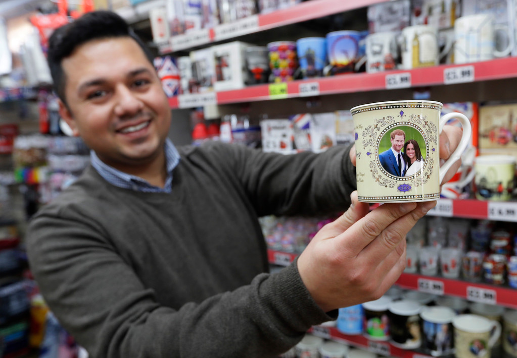 . Salman Qadir, manager of the King and Queen gift shop displays a mug for sale with the image of Britain\'s Prince Harry and Meghan Markle in Windsor, England, Thursday, March 29, 2018. Britain\'s Prince Harry will marry Meghan Markle in Windsor on May 19. (AP Photo/Kirsty Wigglesworth)
