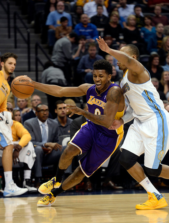 . DENVER, CO - NOVEMBER 13: Los Angeles Lakers small forward Nick Young (0) drives the baseline on Denver Nuggets shooting guard Randy Foye (4) during the third quarter November 13, 2013 at Pepsi Center. (Photo by John Leyba/The Denver Post)