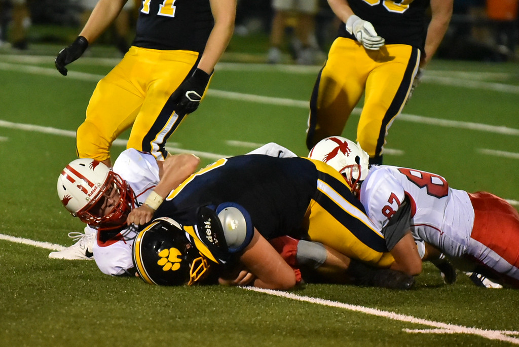 . Littleton senior Mitch Beaudoin (center) is taken down on the Hudson 30 yard line during Friday night\'s match up at home.  Sun/Jeff Porter