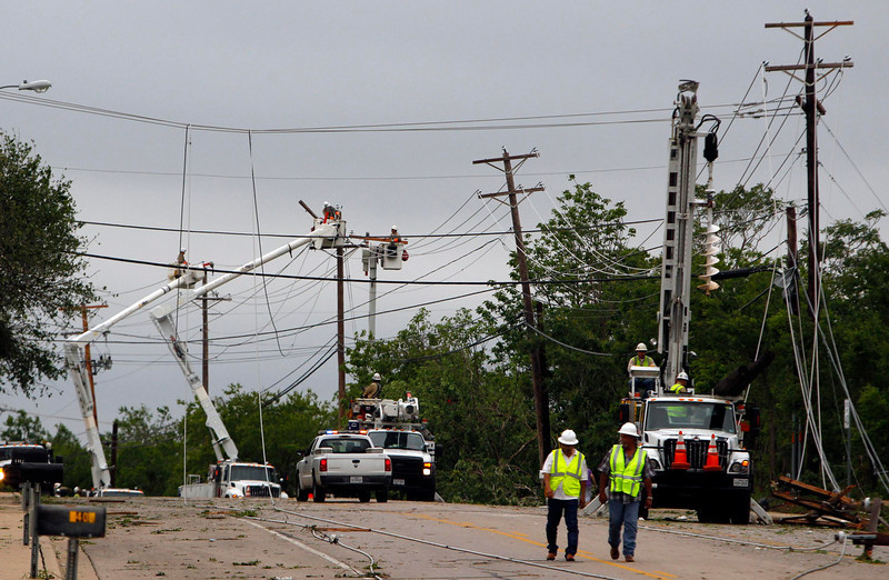 . Utility workers attempt to repair power lines and restore power to a neighborhood after a tornado touched down in Cleburne, Texas May 16, 2013. At least six people were killed and seven were missing after as many as 10 tornadoes ripped through north-central Texas Wednesday evening, leaving a trail of destruction from the worst severe storm outbreak in the United States so far this year.  REUTERS/Richard Rodriguez