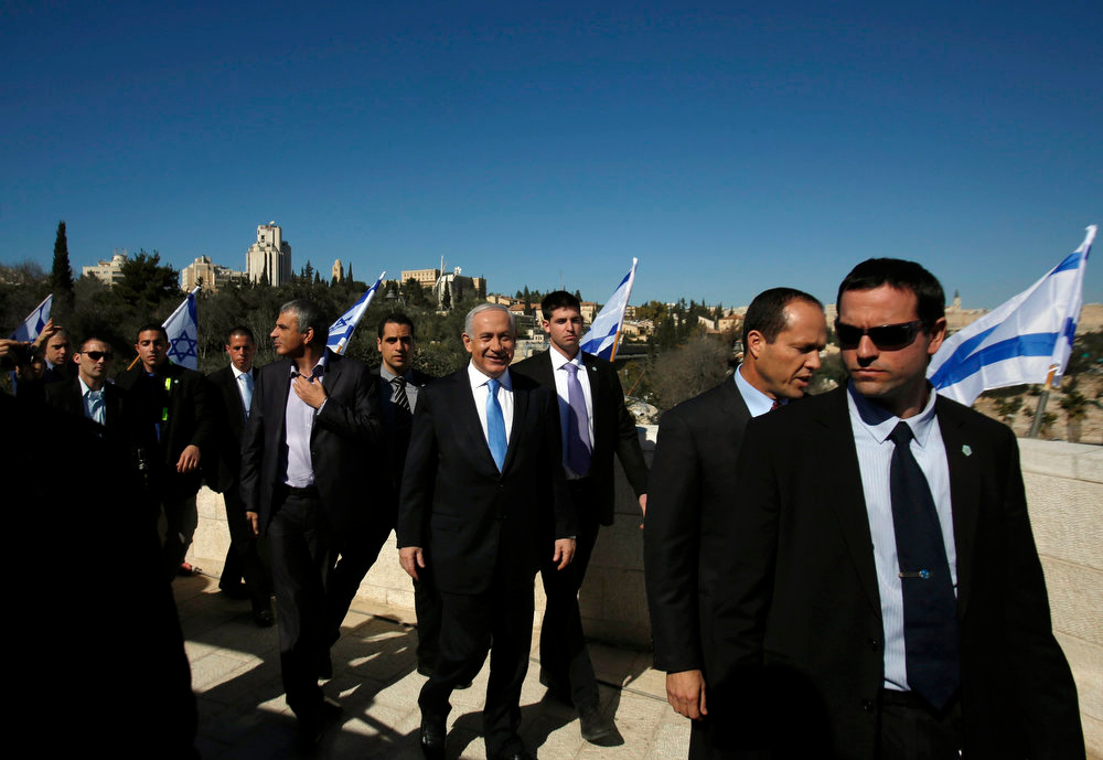 Description of . Israel's Prime Minister Benjamin Netanyahu (C) arrives to give a statement outside the Menachem Begin Heritage Center in Jerusalem January 21, 2013. Netanyahu made an election eve appeal to wavering supporters to