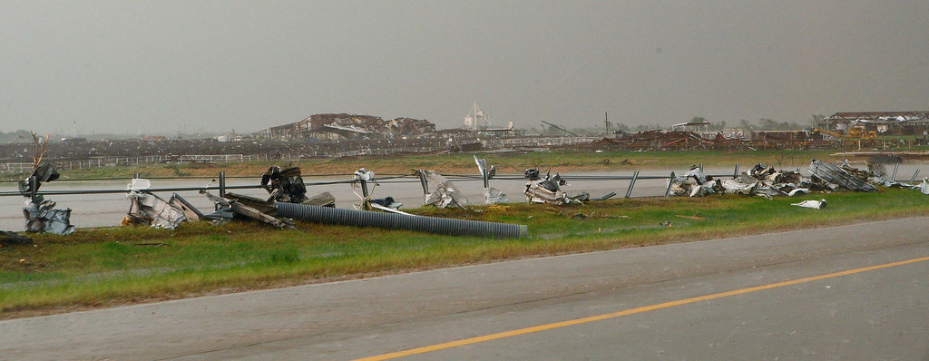 . Tornado debris and a damaged building in the background are seen along Interstate-40 Westbound, just east of El Reno, Oklahoma May 31, 2013. Violent thunderstorms spawned tornadoes that menaced Oklahoma City and its already hard-hit suburb of Moore on Friday, killing a mother and her baby, and officials worried that drivers stuck on freeways could be trapped in the path of dangerous twisters. One twister touched down on Interstate 40 and was headed toward Oklahoma City.  REUTERS/Bill Waugh