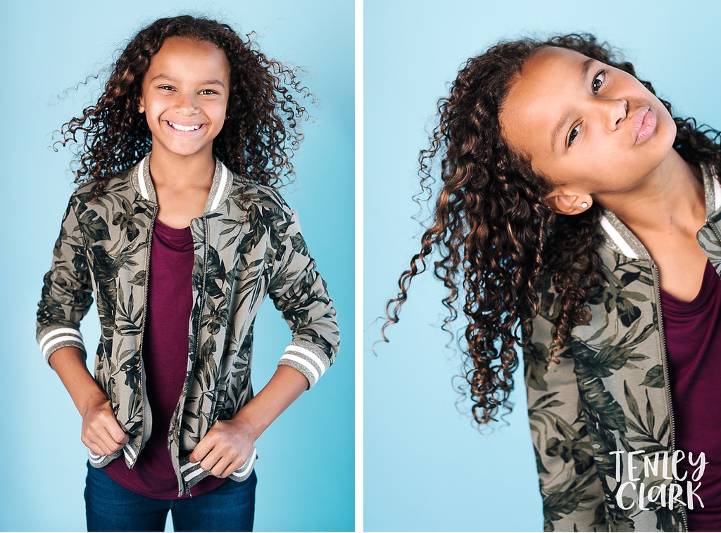 Playful, colorful studio kids headshots by Tenley Clark Photography. Girl blue backdrop in jean and camo look.