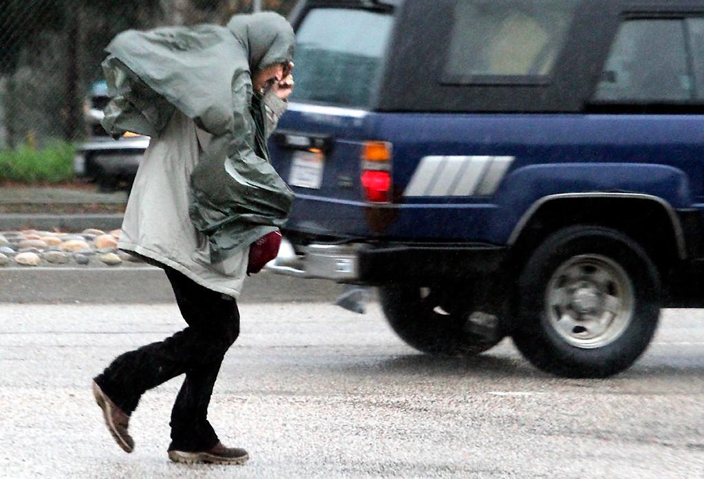 . A man walking along River Street in Santa Cruz braces himself against the wind Thursday morning, Dec. 11, 2014. (Shmuel Thaler -- Santa Cruz Sentinel)
