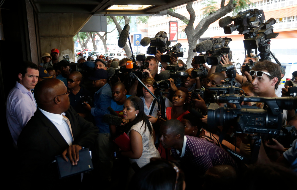 Description of . Journalists wait outside the Pretoria Magistrates court during the bail application of
