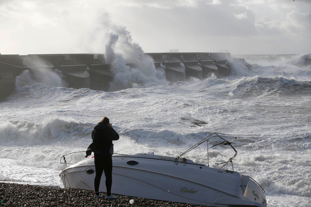 . A boat lays stricken on the strand as people watch the waves batter into the sea wall of a marina in Brighton, south England, Monday, Oct. 28, 2013.  (AP Photo/Sang Tan)