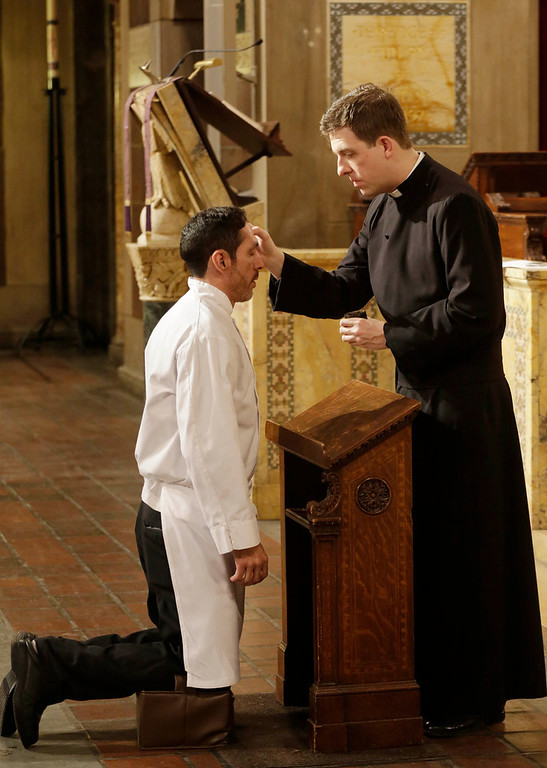 . The Rev. Matthew Moretz applies ashes to hotel chef Jose Davila during an Ash Wednesday observance at St. Bartholomews Episcopal Church, Wednesday, March 5, 2014, in New York. Some Protestant, and all Catholic churches, distribute ashes on the forehead as a sign of repentance and renewal on Ash Wednesday as the 40-day season leading to Easter begins. (AP Photo/Mark Lennihan)