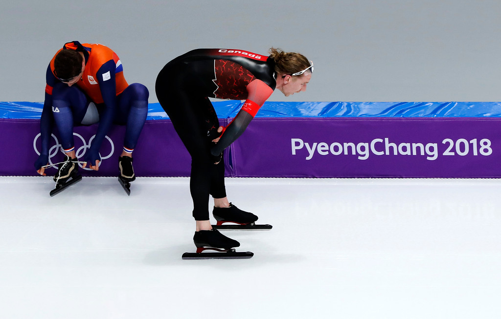 . Gold medallist Ted-Jan Bloemen of Canada passes Sven Kramer of The Netherlands who ties his skates for his race on the men\'s 10,000 meters speedskating race at the Gangneung Oval at the 2018 Winter Olympics in Gangneung, South Korea, Thursday, Feb. 15, 2018. (AP Photo/Eugene Hoshiko)