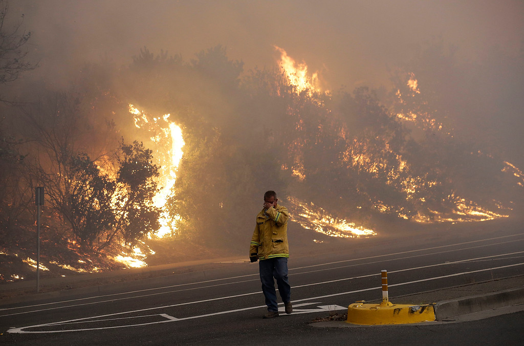 . A firefighter covers his eyes as he walks past a burning hillside in Santa Rosa, Calif., Monday, Oct. 9, 2017. Wildfires whipped by powerful winds swept through Northern California, sending residents on a headlong flight to safety through smoke and flames as homes burned. (AP Photo/Jeff Chiu)