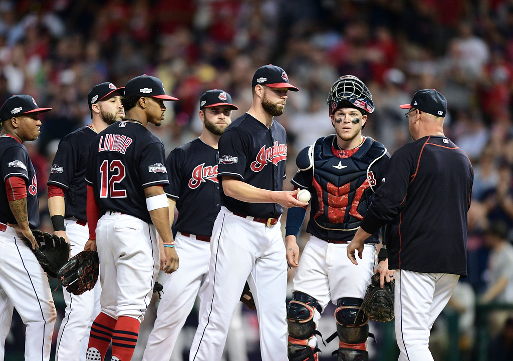 . Cleveland Indians pitcher Corey Kluber, third from right, hands the ball to manager Terry Francona, right, in the eighth inning during Game 2 of baseball\'s American League Division Series against the Boston Red Sox, Friday, Oct. 7, 2016, in Cleveland. (AP Photo/David Dermer)