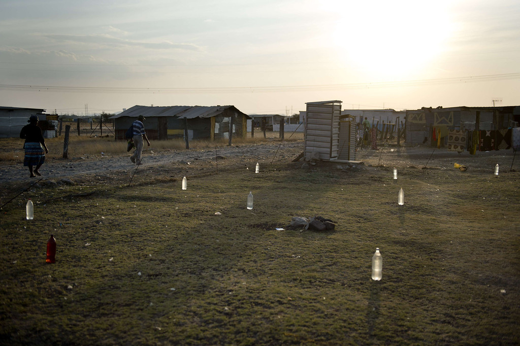 . Bottles filled with water are laid out on a lawn to prevent stray dogs from fouling it on July 9, 2013 in the Nkaneng shantytown next to the platinum mine, run by British company Lonmin, in Marikana. On August 16, 2012, police at the Marikana mine open fire on striking workers, killing 34 and injuring 78, during a strike was for better wages and living conditions. Miners still live in dire conditions despite a small wage increase.  ODD ANDERSEN/AFP/Getty Images