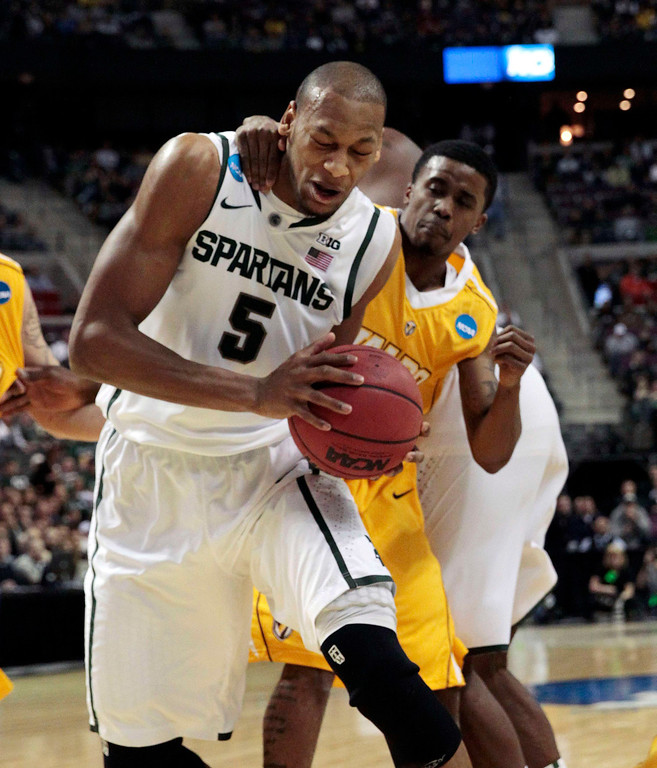. Michigan State Spartans\' Adreian Payne is fouled by Valparaiso Crusaders\' Erik Buggs during the first half of their second round NCAA tournament basketball game in Auburn Hills, Michigan March 21, 2013. REUTERS/Jeff Kowalsky