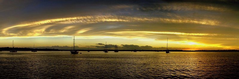 Yellow and gold coloured cirrostratus cloudy coastal nautical Sunset Seascape panorama. Tin Can Bay, Queensland, Australia.