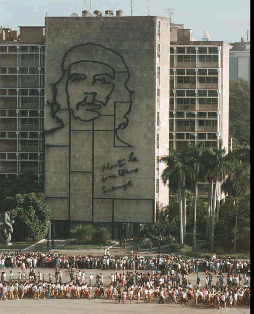 """. Seen in front of a sign depicting Ernesto \""""Che\"""" Guevara, some of the several thousand Cubans wait in line to get a glimpse of the remains of the revolutionary hero Saturday, Oct. 11, 1997 in Havana, Cuba at the Plaza of the Revolution. The remains will be on display in Havana until Oct. 14 when they will be taken to Santa Clara in a caravan and entombed in a mausoleum on Oct 17. (AP Photo/Joe Cavaretta)"""