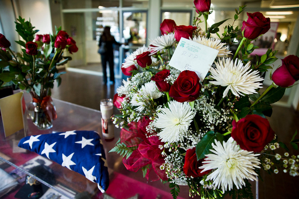 . Flowers are left for at a makeshift memorial for the dead San Bernardino sheriff\'s deputy at Sheriff\'s Headquarters on Wednesday, Feb. 13, 2013. The deputy was killed during a shootout with ex-LAPD officer Christopher Dorner in Big Bear yesterday.  (SGVN/Staff photo by Watchara Phomicinda)