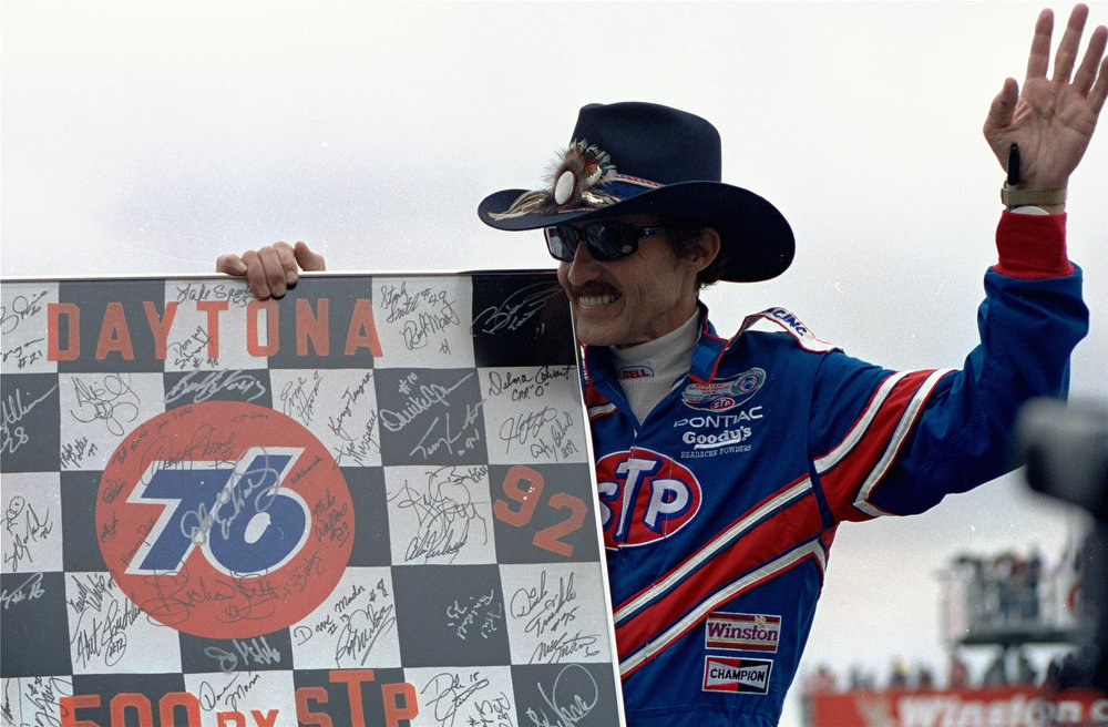 Description of . Richard Petty of Randleman, N.C., waves to the crowd during pre-race festivities before Sunday, Feb. 16, 1992 running of the Daytona International Speedway.  Petty, 54, competing in his 32nd Daytona 500, has announced he will retire at the end of the racing season. (AP Photo/Chris O\'Meara)