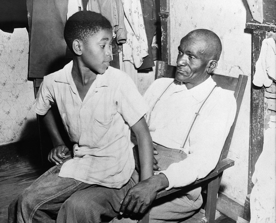 . Mose Wright, right, and his son Simeon, sit in their home in Money, Miss., near Greenwood, and discuss the loss of their 14-year-old relative, Emmett Till, September 1, 1955. Till was a nephew of Mose Wright. Till\'s body was found in the Tallahatchie River August 31. He had a bullet hole in his head. Two white men are being held in jail at Greenwood in connection with the death. (AP Photo)