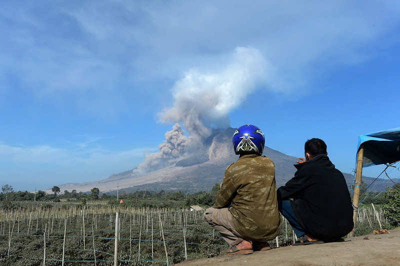 . Indonesian villagers watch as mount Sinabung spews smoke and hot ash in Karo on February 4, 2014. A volcano in western Indonesia that killed 15 people in a weekend eruption shot hot ash and rocks high into the air again on February 3, halting a search for any more victims. (ADEK BERRY/AFP/Getty Images)