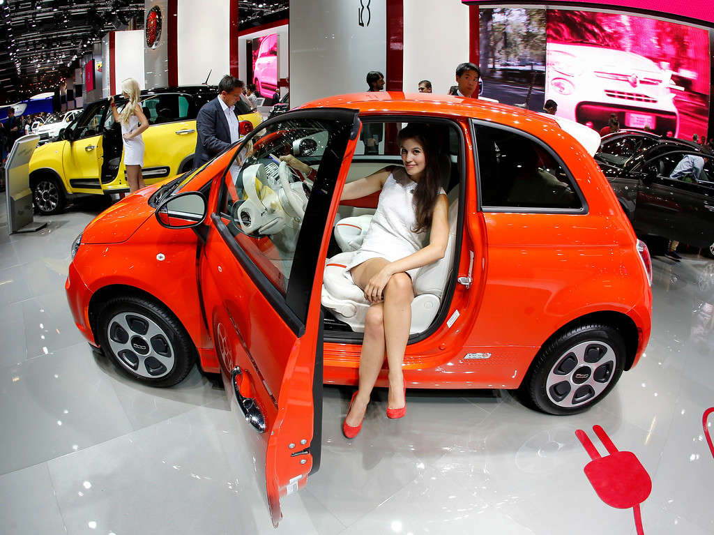. A hostess sits in a Fiat 500 during the first press day of the 65th Frankfurt Auto Show in Frankfurt, Germany, Tuesday, Sept. 10, 2013.  (AP Photo/Michael Probst)