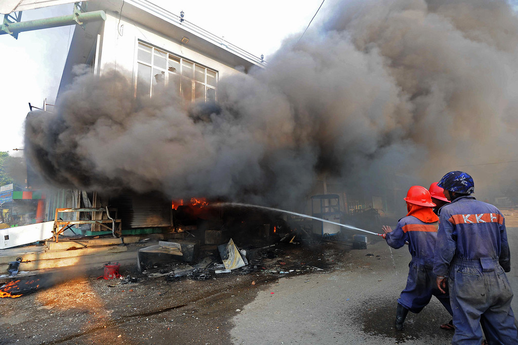 . Firefighters use a hose to extinguish a fire at a house in riot-hit Meiktila, central Myanmar on March 22, 2013.     AFP PHOTO/ Soe Than WIN/AFP/Getty Images