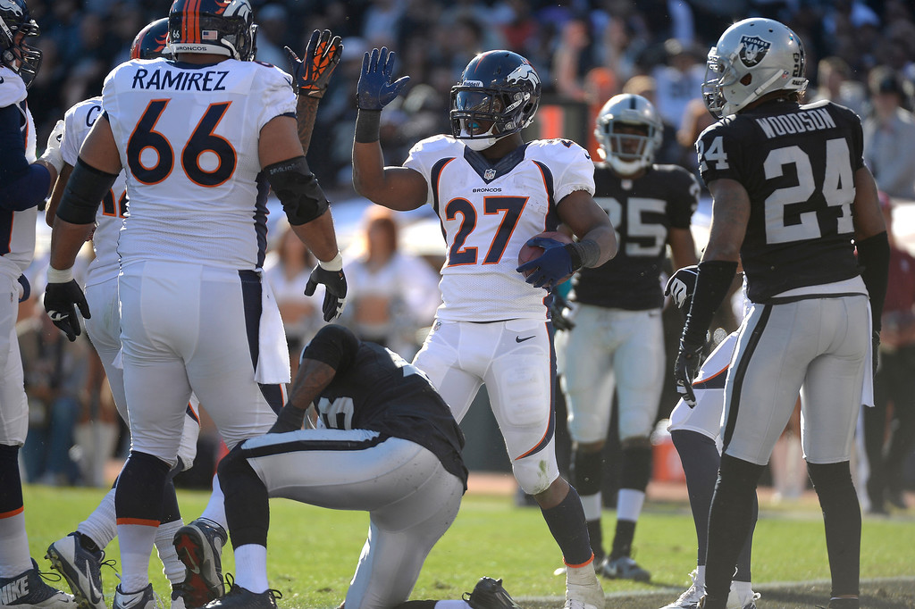 . Denver Broncos running back Knowshon Moreno (27) high fives Denver Broncos wide receiver Andre Caldwell (12) after his touchdown run in the first quarter against the Oakland Raiders at O.co Coliseum. (Photo by John Leyba/The Denver Post)