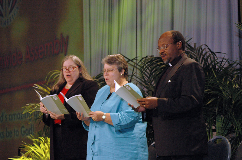 The Rev. Deborah DeWinter, program executive for U.S. for the World Council of Churches, Clare Chapmann, deputy general secretary for adminstration and finance for National Council of Churches of Christ in the USA and Dr. Ishmael Noko, general secretary, Lutheran World Federation rise to sing a hymn that was specially commissioned for the Lutheran World Federation's 60th anniversary.