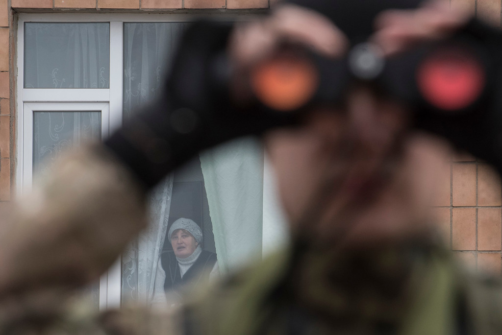 . A Ukrainian serviceman watches through binoculars positions of pro-Russian rebels as a local woman looks from a window in the village of Chermalyk, eastern Ukraine, Thursday, Feb. 26, 2015. In a long-awaited development, Ukrainian forces and separatist fighters both announced Thursday they are pulling back heavy weapons from the front line in eastern Ukraine. (AP Photo/Evgeniy Maloletka)